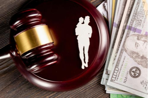 Paper mother and child figures, judge's gavel with money, adoption costs in Charlotte, NC