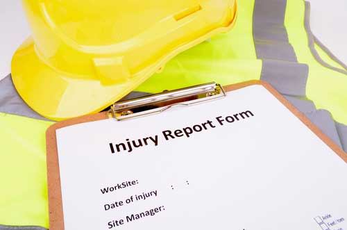 hard hat, clipboard with injury report form, reporting a work injury in Charlotte