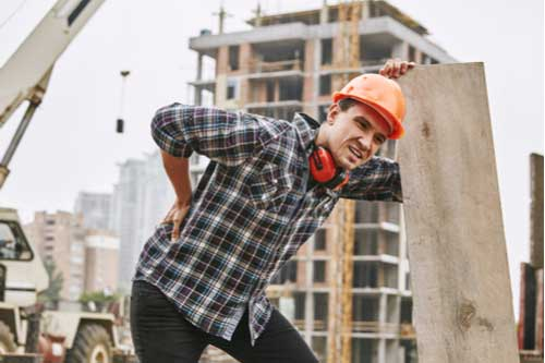 Young construction worker rubbing his injured back, Mooresville workers' compensation lawyer concept