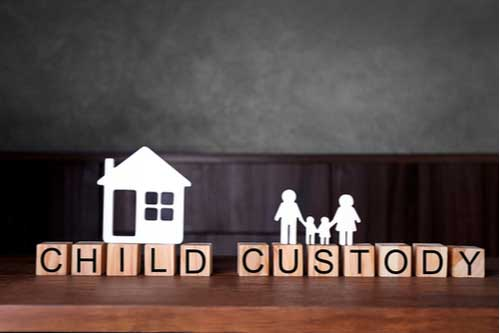 Paper cutout house and family on blocks with words child custody. Charlotte child custody lawyer concept