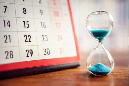 Hourglass and calendar, concept of time limit for workers' comp claim in North Carolina