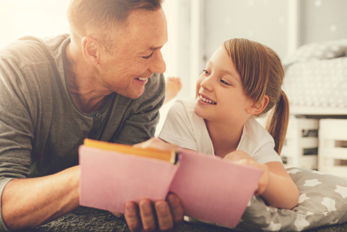 This is an image of a father reading with daughter concept of child custody with help of Statesville divorce lawyer