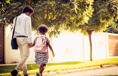 Father and daughter walking through a park after calling a Charlotte child support lawyer
