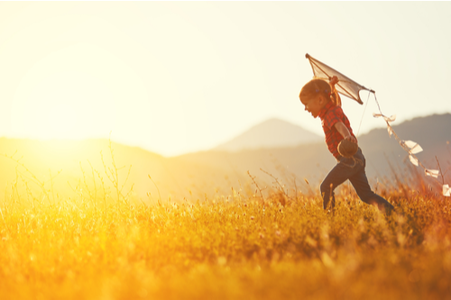 This is an image of a happy child flying a kite after the help of a Charlotte child support lawyer