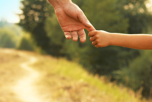 Parent holding a child's hand after calling a Charlotte child support lawyer