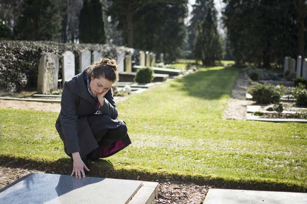 Woman at grave who deserves workers' comp death benefits